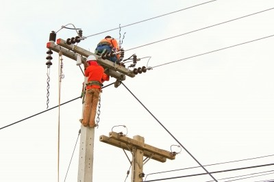 Electricians working on power pole